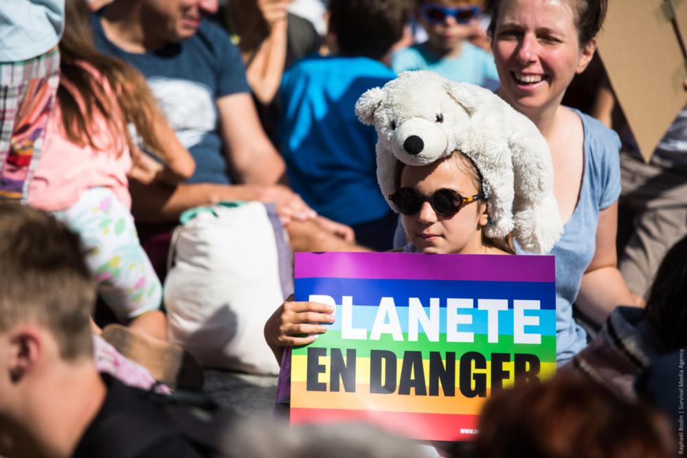 A girl with a white bear, at the march in Paris.